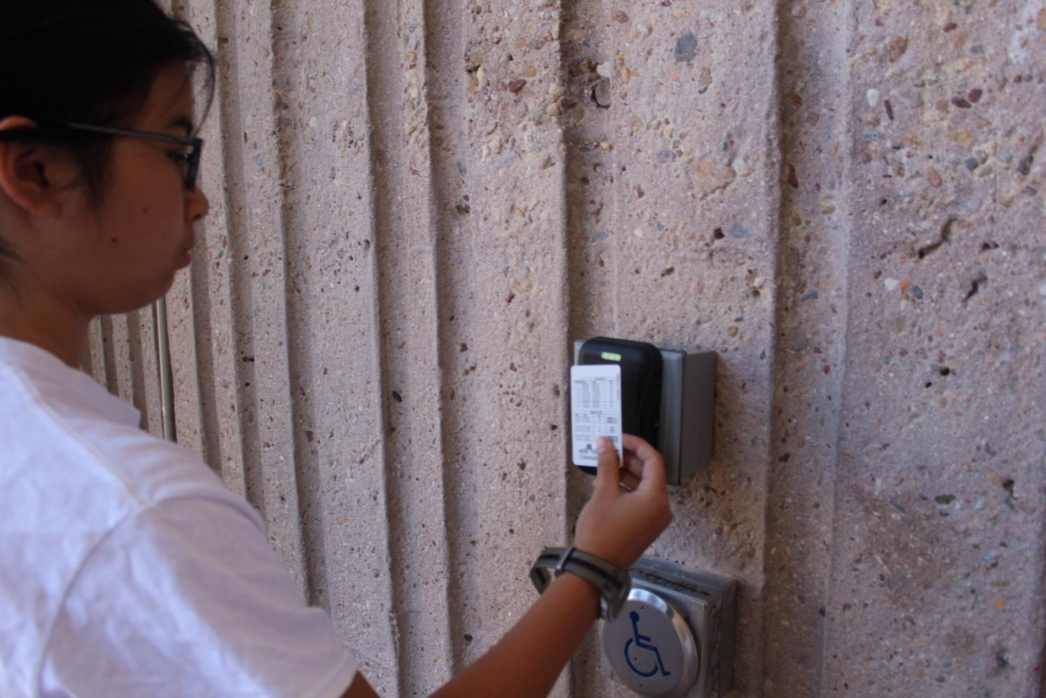 Phoebe Wu, freshman, scans her ID card at the bottom of the school to get inside during seventh period.