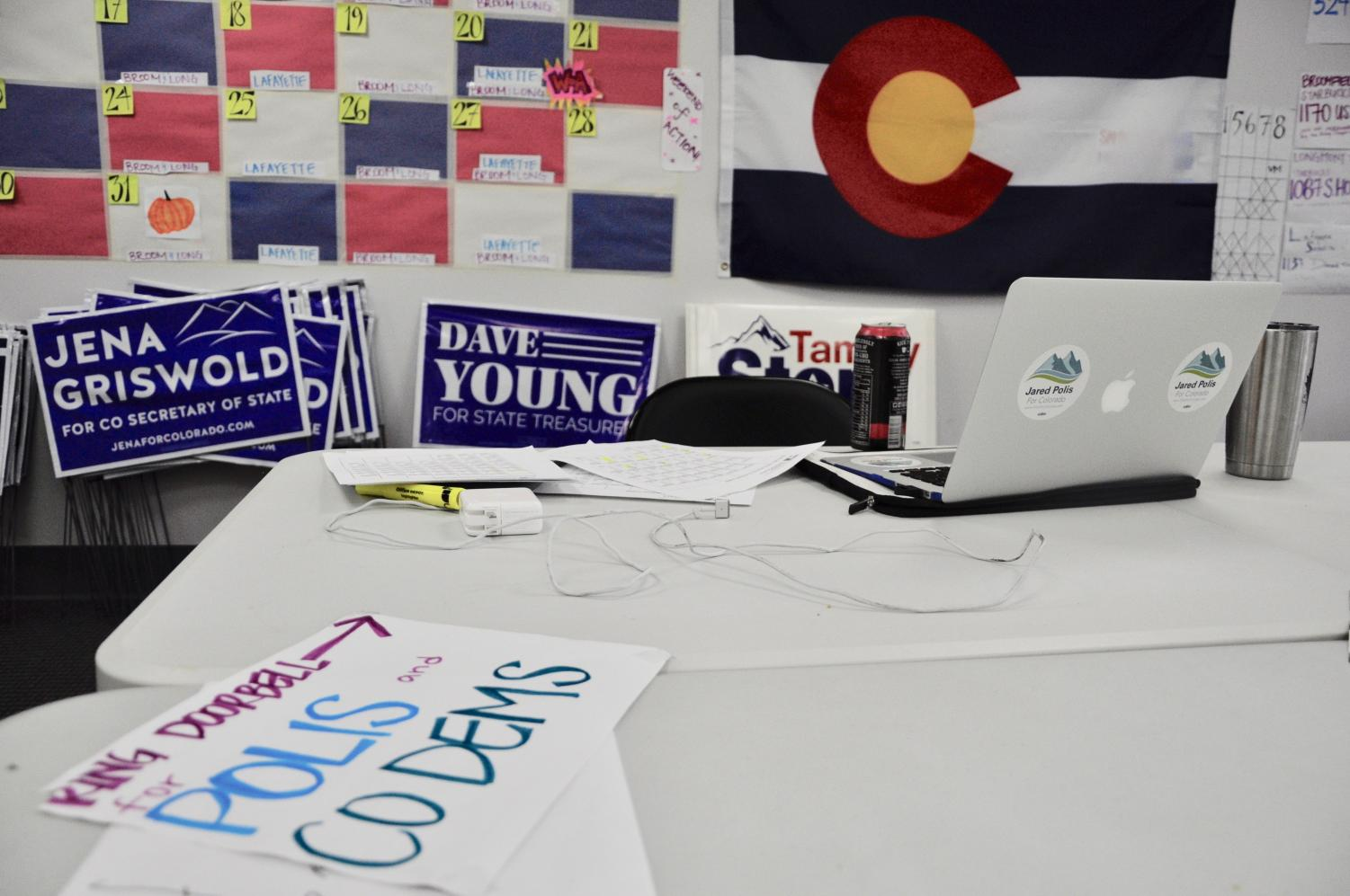 Signs, paperwork and flags clutter a table at the Polis Campaign office. Many interns are given the responsibility of getting out information on the Polis Campaign.