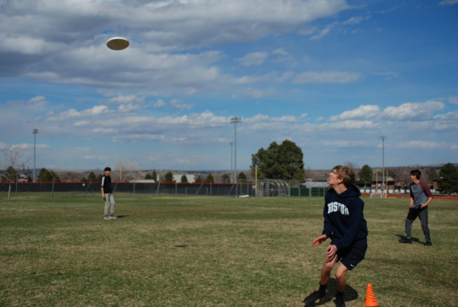 Fairview+ultimate+frisbee+team+members+rush+to+catch+a+pass+during+practice.