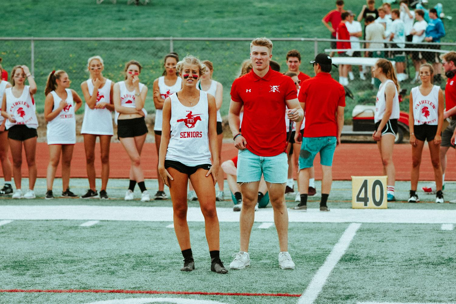 Seniors Matt Greenwald and Emma Carter look out to the field during a timeout in the first half of the powderpuff football game.