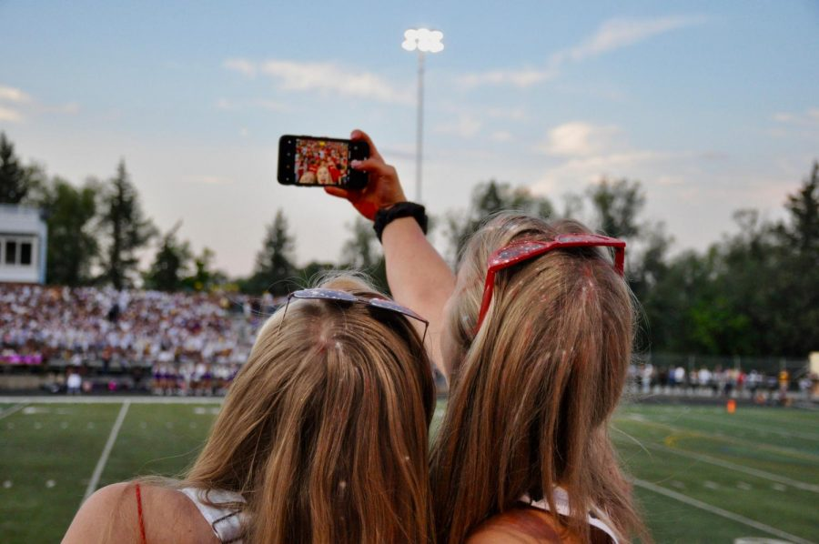 Two Seniors take a selfie at halftime.