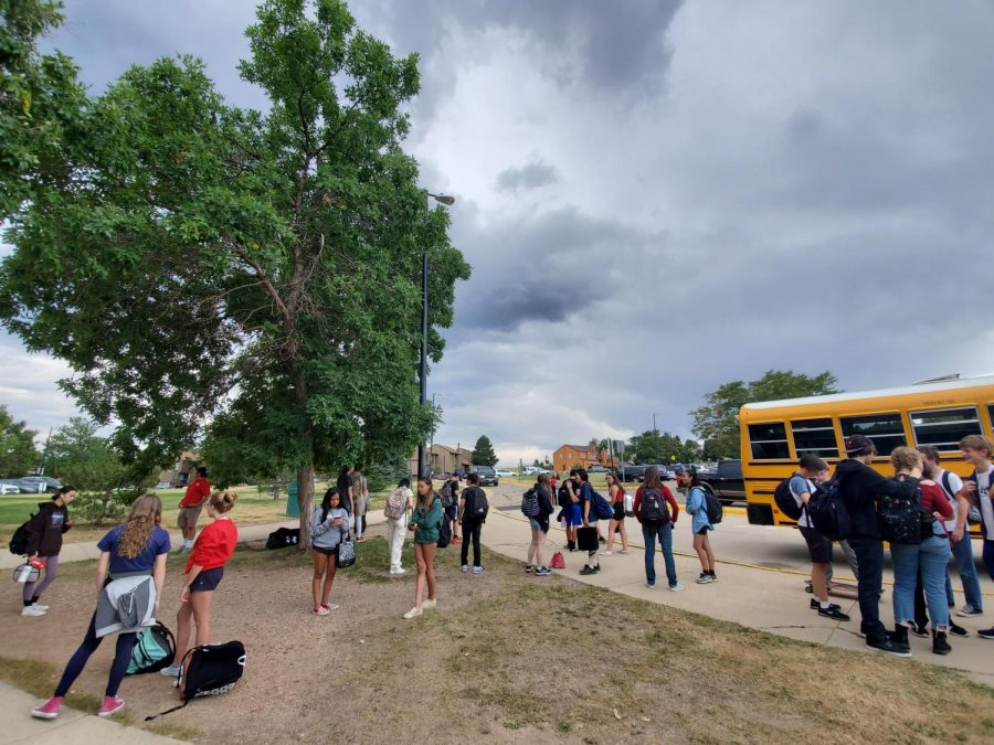 Students wait for the school bus at the end of the day.