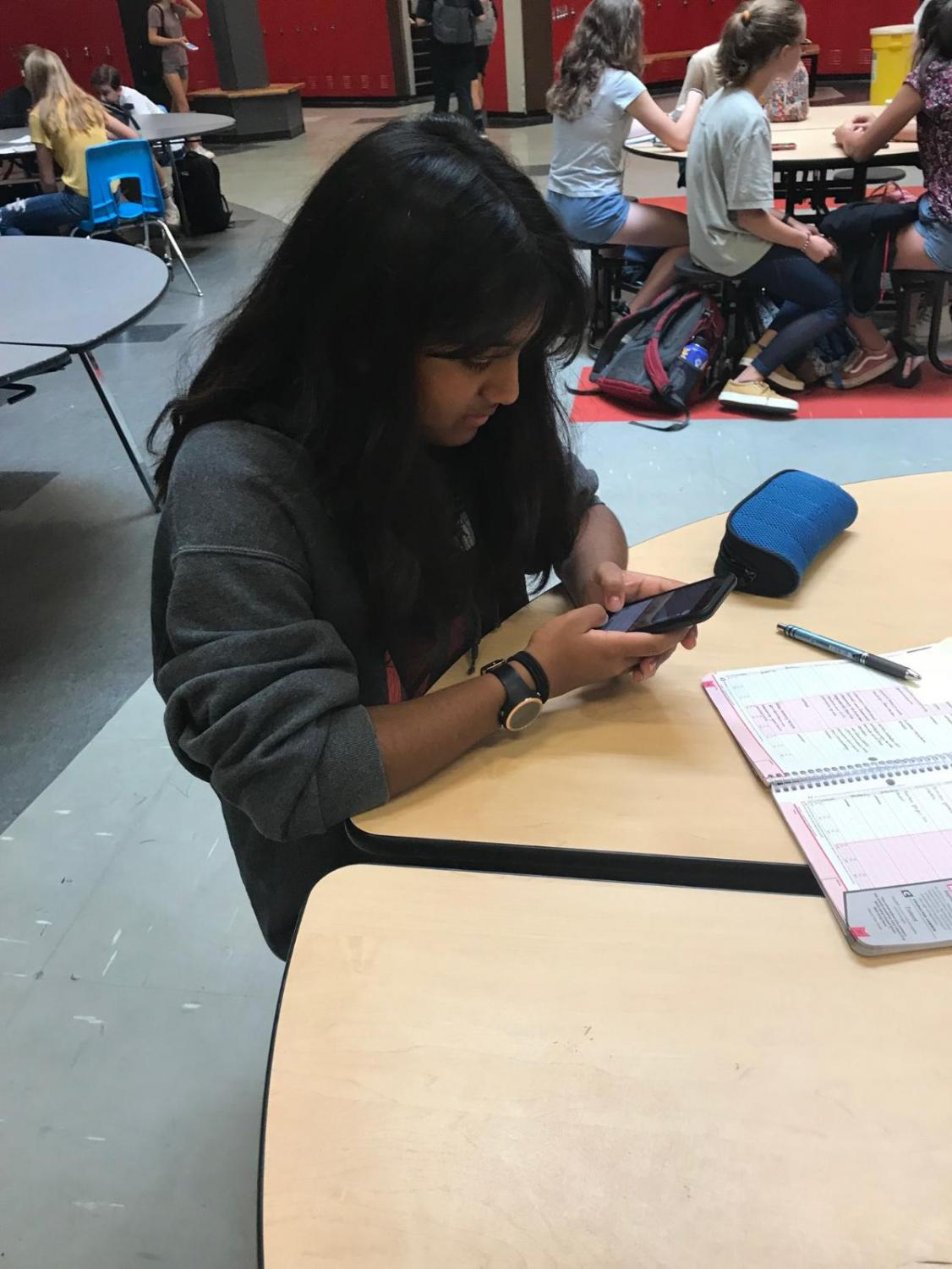 Hyumi Wijesakara looking at her phone during CAT time in the Student Center.