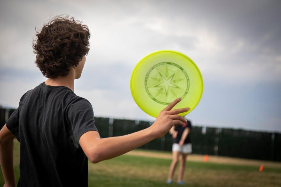 Sophomore Benji Dienstfrey throws a frisbee during Ultimate Frisbee drills at practice.