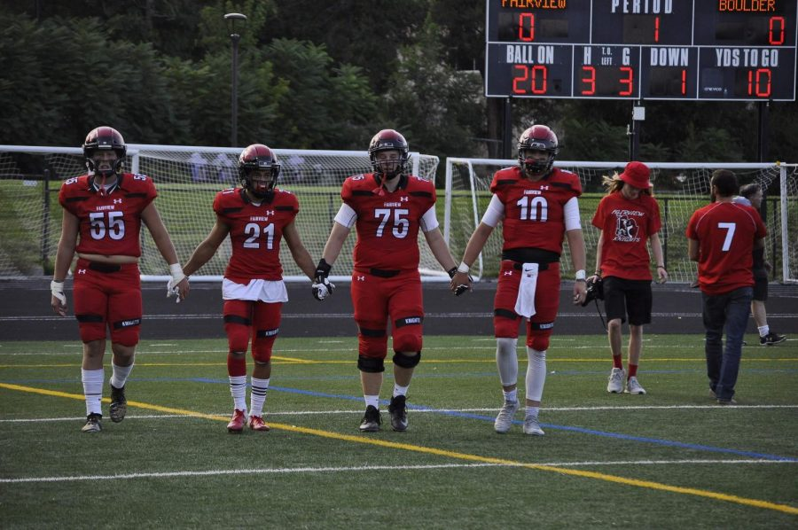 Captains of the football team holding hands to demonstrate strong team spirit.