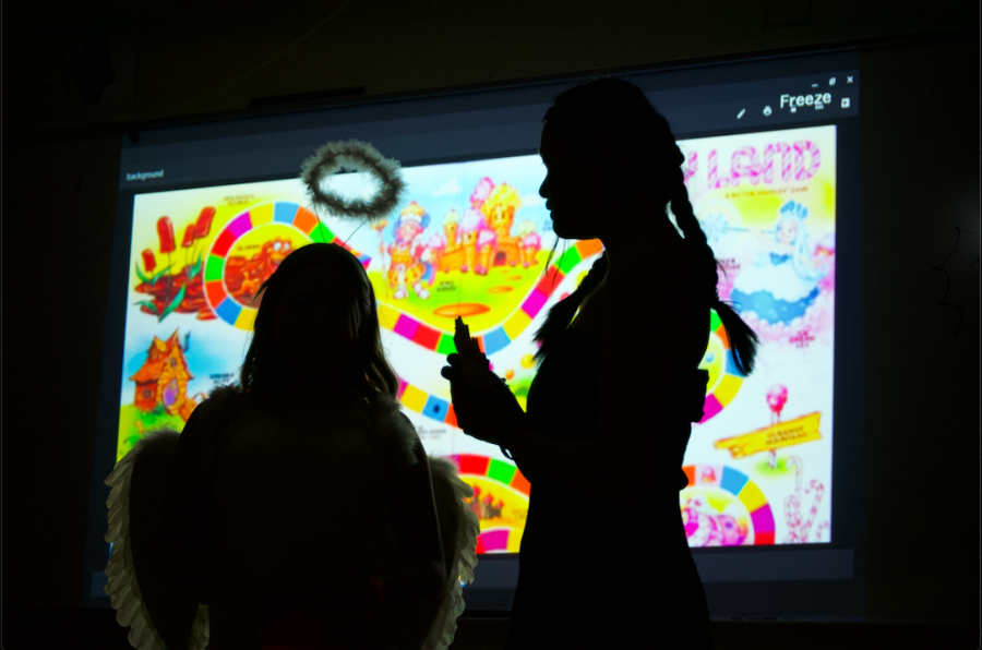 Kids did math to progress and get candy in Math Honor Society's Candyland themed room. In this picture, the glow of Candyland illuminates two kids in the Math Honor Society room.